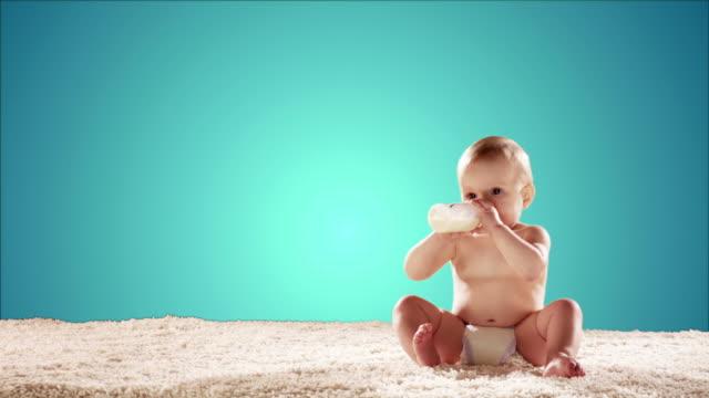 Baby drinks milk then tosses it aside. video
