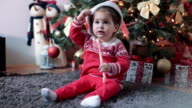 baby eating candy under the christmas tree video