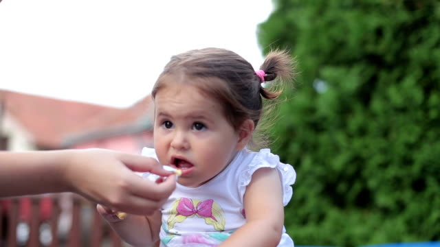 baby eating cookies outdoor in a backyard video