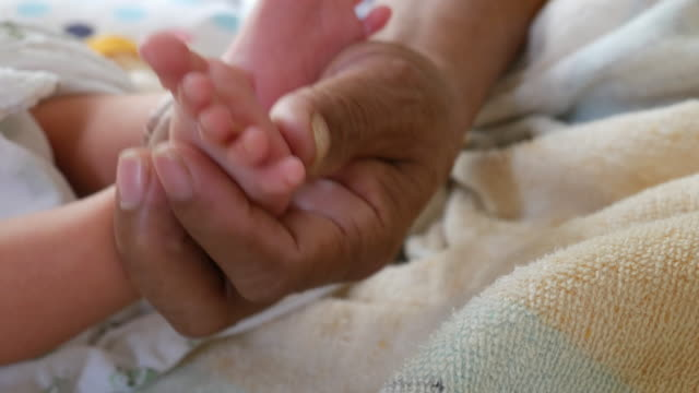 Baby feet in mother hands. Newborn Baby's feet on female video