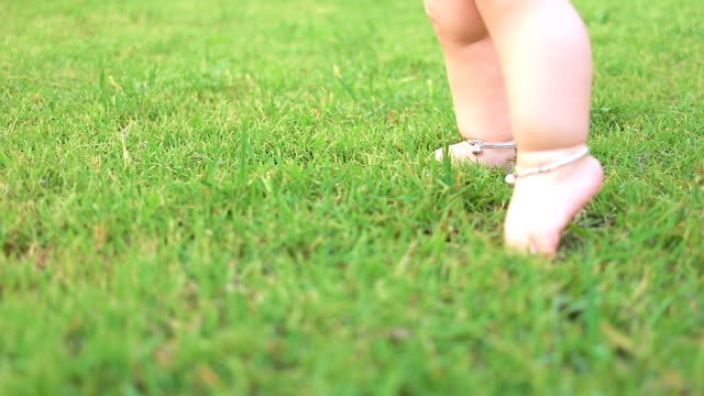 Baby first steps on grass, slow motion, dolly shot. video