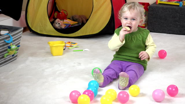 Baby girl eat cookie and play with colorful balls in play room. video