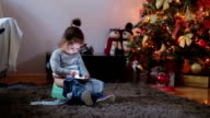 Baby girl looking at smart phone and sitting on a potty near a Christmas tree video