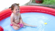 Baby girl making faces in the pool and having fun video