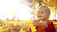 SLO MO Baby girl playing with autumn leaves video