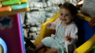 Baby girl plays in a amusement ride at night - having fun and laughing loud video