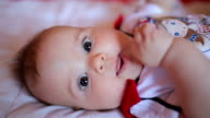 Baby girl puting hand in her mouth,close up video