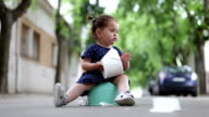 baby girl sitting on a potty outdoors and holding toilet paper video