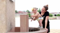Baby girl (12-18 months) standing on a public water tap, trying to catch water jet and laughing video