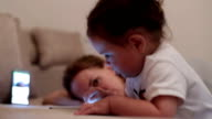 Baby girl using smart phone - touching and watching on the screen video