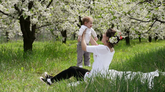 Baby held by his mother in the meadow video