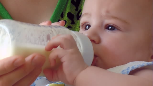 Baby holds a bottle of milk and eating video