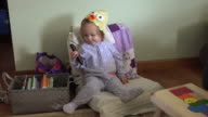 Baby in duck hat sitting on small chair tv remote playing with tongue. video