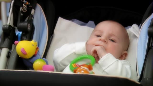 Baby in the pram sucks thumb - medium shot video