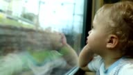 Baby looking out train window. Cute toddler blonde baby boy looking out window landscape video