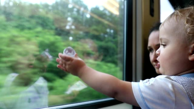Baby looking out train window. Cute toddler blonde baby boy looking out window landscape. Mother holding baby on train video