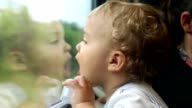 Baby looking out train window. Toddler looking out at landscape passing while traveling by train video