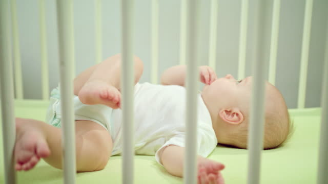 Baby Lying in a Crib at Home Eating its Fingers video