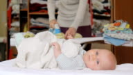 Baby lying on bed and her mother's ironing. video
