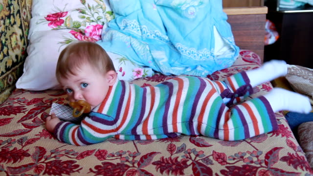 Baby lying on the bed and playing with playing cards in her hands video