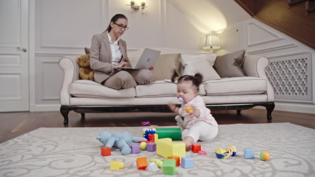 Baby of mom entrepreneur playing on carpet video