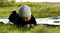 Baby on a blanket exploring the grass. video
