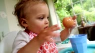 Baby playing with food. Happy toddler blonde baby boy having fun with food leftovers. Over head shot of baby's fingers playing with plate and food video
