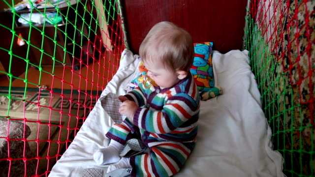 Baby playing with playing cards in her crib video