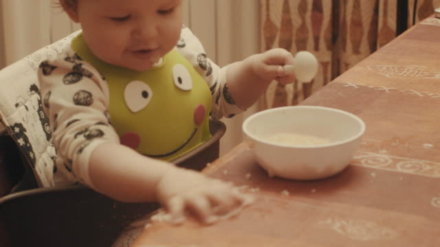 Baby playing with the porridge and somebody feeding her video