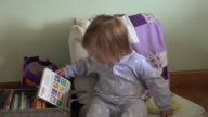 Baby shaking head no being silly on small chair looking at books. video