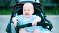 baby sitting in the baby carriage in park video
