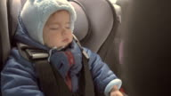 baby sleeping in her car seat. A child in a warm winter clothes. video