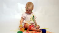 Baby soiled by paints holds brushes in hand video