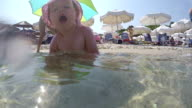 Baby splashes the water in the sea, sitting and playing video