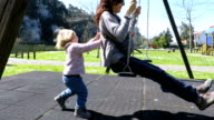 baby swinging mother in playground park video