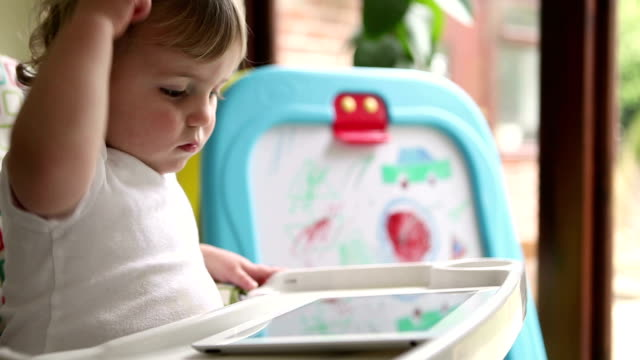 Baby toddler playing with a digital tablet in high chair video