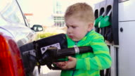Baby using a Gasoline Pump at the Gas Station video