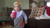 Baby with homemade duck hat drinking from pink sippy cup. video