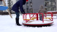 Babysitter woman and baby girl spin on circle swing in playground in yard. FullHD video