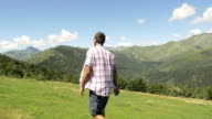 Back and side view of young man hiking in mountain outdoor nature scenery during sunny summer day - gimbal steadicam HD video footage video