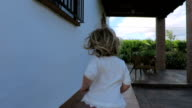 back blonde baby running exterior to door house slow motion video