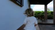 back blonde baby running exterior to door house video