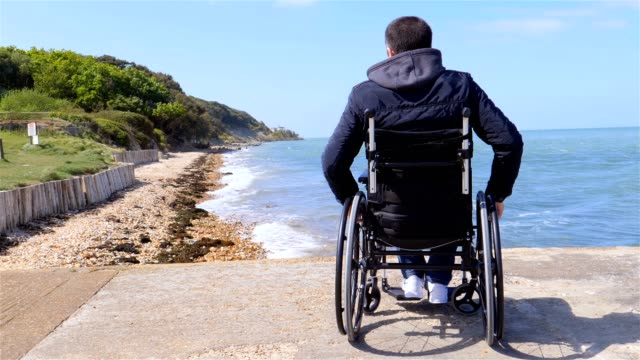 Back of disabled man in wheelchair at beach video