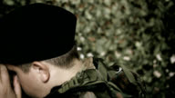 back of the head of a soldier in front of camouflage net video