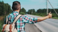 Back side of boy stay with backpack thump up at road in summer day. Hitchhiking video