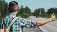 Back side of boy with backpack hitchhiking at road in summer sunny day. Thumb up video