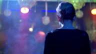 Back side of Dj girl in black top spinning at turntable in nightclub. Smoke video