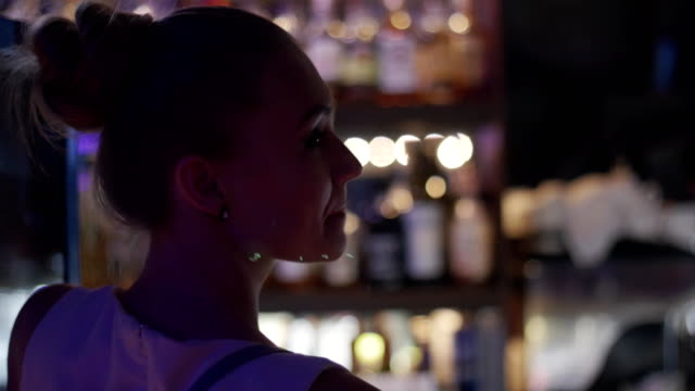 Back side of girl at bar stand on party in nightclub. Shake head. Cheering video