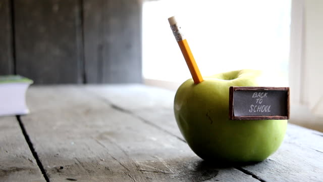 Back to school background - inscription and pencil and apple on the table video