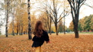 back view happy cute little girl with curly hair runing through the autumn alley in the park slow mo video